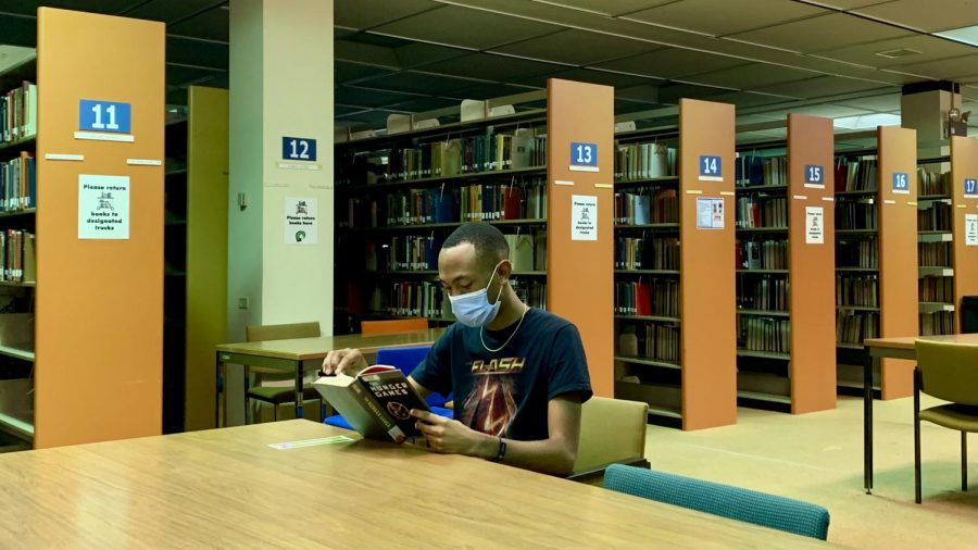 Kamarreo Jernigan wearing a mask while reading in the Eugene P. Watson Memorial Library.